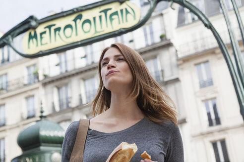 France, Paris, portrait of young woman eating baguette - FMK001253
