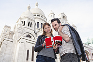 France, Paris, portrait of couple with travel guide in front of Sacre Coeur - FMKF001357