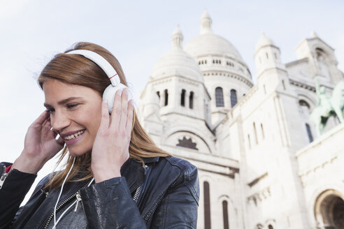 France, Paris, portrait of happy young woman listening music with headphones in front of Sacre Coeur - FMKF001262