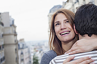 France, Paris, portrait of smiling young woman hugging her partner - FMKF001271