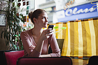 France, Paris, portrait of young woman using her smartphone in a cafe - FMKF001279