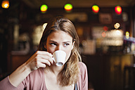 France, Paris, portrait of young woman drinking cup of coffee in a cafe - FMKF001288