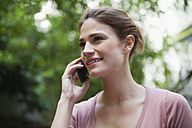 France, Paris, portrait of young woman telephoning with her smartphone - FMKF001291