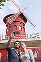 France, Paris, couple photographing  themself with smartphone in front of famous Moulin Rouge - FMK001300