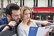 France, Paris, couple looking at a city map - FMKF001306