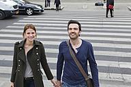 France, Paris, couple walking hand in hand on crosswalk - FMKF001312