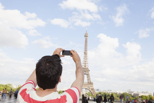 France, Paris, man photographing Eiffel Tower with his smartphone, back view - FMKF001334