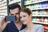France, Paris, couple photographing  themself with smartphone - FMKF001323