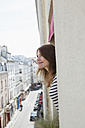 France, Paris, portrait of smiling young woman looking out of hotel window - FMKF001329