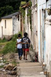 Brazil, Mato Grosso, Poxoreo, mother and son walking arm in arm in a favela - FLK000352