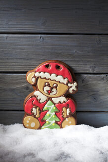 Gingerbread bear standing on artificial snow in front of grey wooden wall - CSF021670
