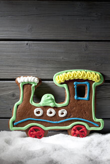 Gingerbread locomotive standing on artificial snow in front of grey wooden wall - CSF021673