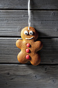Smiling gingerbread man hanging in front of grey wooden wall - CSF021676