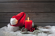 Lighted red candle and Christmas cap on artificial snow in front of grey wooden wall - CSF021679