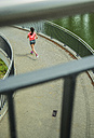 Young woman jogging on a bridge, back view - UUF000950
