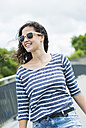 Portrait of smiling young woman wearing sunglasses - UUF000968