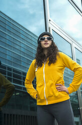 Young woman wearing yellow tracksuit top, wool cap and sunglasses - UUF000976