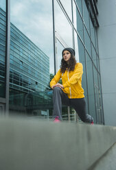 Young woman wearing yellow tracksuit top making stretching exercises - UUF000977