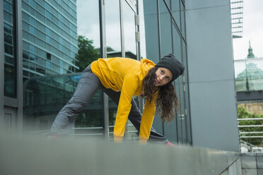 Young woman wearing yellow tracksuit top making stretching exercises - UUF000978