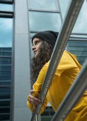 Portrait of young woman wearing yellow tracksuit top leaning on railing - UUF000983