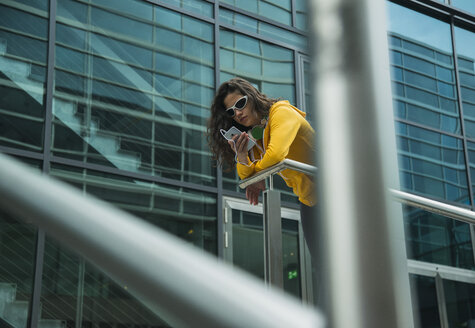 Young woman wearing yellow tracksuit top using smartphone - UUF000987