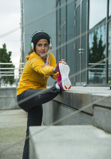 Young woman wearing yellow tracksuit top making stretching exercises - UUF000992
