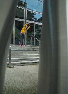 Young woman wearing yellow tracksuit top making stretching exercises - UUF000994