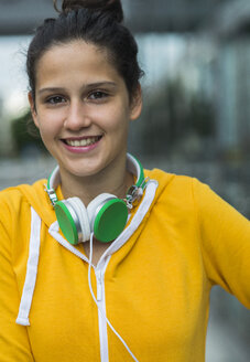 Portrait of smiling young woman wearing yellow tracksuit top - UUF000996