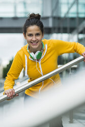 Portrait of smiling young woman wearing yellow tracksuit top - UUF000998