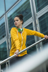 Portrait of young woman wearing yellow tracksuit top - UUF001000