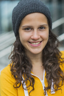 Portrait of smiling young woman wearing yellow tracksuit top and wool cap - UUF001002