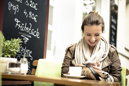 Smiling young woman sitting in street cafe using smartphone - FX000023