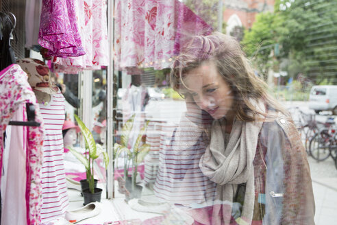 Germany, young woman looking at clothes in window display - FX000019
