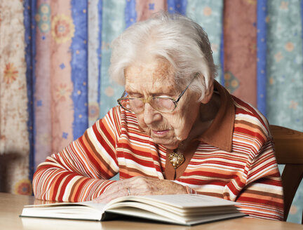 Portrait of senior woman reading a book - WWF003337