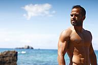 Greece, Ionic Islands, Corfu, shirtless man enjoying sunlight in front of the sea - AJF000071