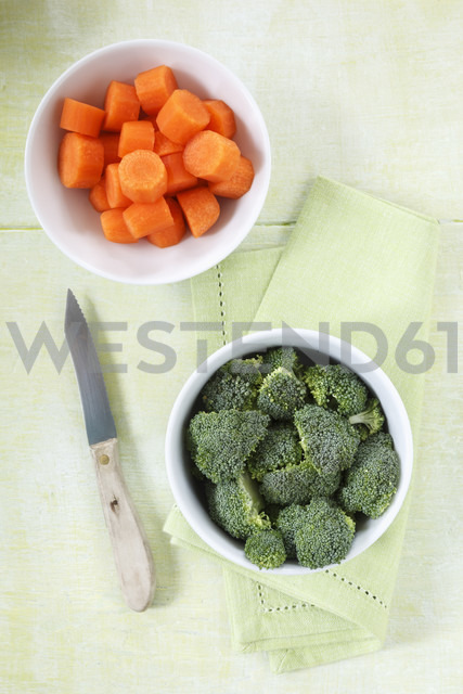 Bowls of broccoli florets and sliced carrots, kitchen knife and cloth on wood - EVGF000692
