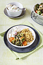 Bowl of vegetarian pistachio curry dish with pilaf and raita - EVGF000707