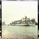 Container ship being towed across the North Elbe, Elbe Philharmonic Hall in the background, Hamburg, Germany - SE000728