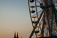 Germany, North Rhine-Westphalia, Cologne, Cologne cathedral and part of big wheel at sunset - WGF000319