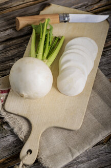 Whole and sliced turnips, Brassica rapa subsp. rapa var. majalis and knife on kitchen board and wood - ODF000738