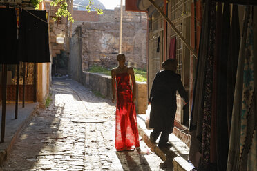 Turkey, Diyarbakir, display figure with red skirt standing at alley in old city - SIE005439