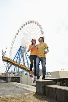 Happy young couple on a funfair - RHF000350