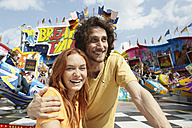 Happy young couple on a funfair - RHF000357