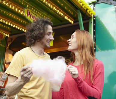 Happy young couple on a funfair with cotton candy - RHF000360