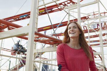 Smiling young woman on a funfair - RHF000379