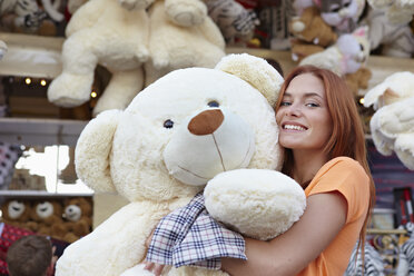 Happy young woman on a funfair hugging large teddy bear - RHF000369