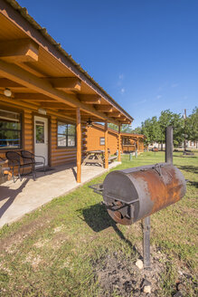 USA, Texas, Log homes with BBQ smoker in front - ABAF001353