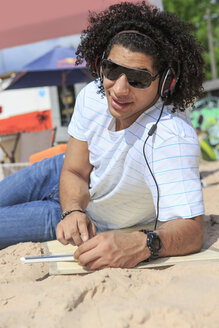 Portrait of a young man with digital tablet listening music on the beach - VTF000299