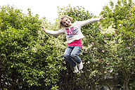 Little girl jumping on trampoline - STB000186