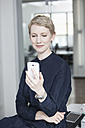 Germany, Munich, Businesswoman in office, using smart phone - RBYF000529